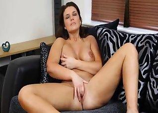 Soloing busty brunette rubs her wet cunt